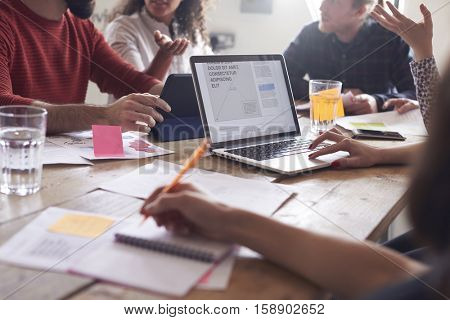 Close Up Of Designers Meeting Around Table In Office