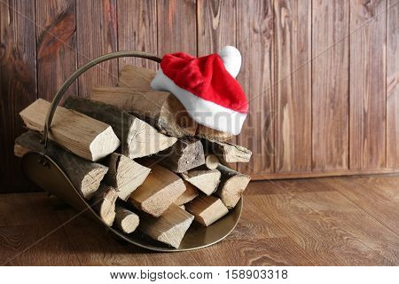 Basket with firewood and Santa Claus hat on wooden background