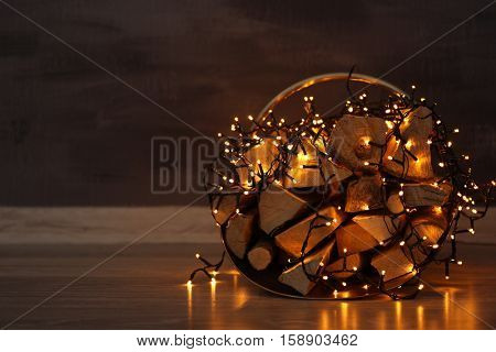 Basket with firewood and garland on dark blurred background