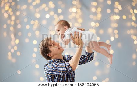 family, fatherhood and parenthood concept - happy smiling young father with little baby over holidays lights background