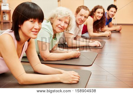 Group with senior woman at rehab at health club