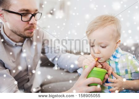 family, childhood, fatherhood, care and people concept - father helping little son with drinking from cup at home over snow