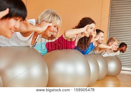 Pilates class training their back with gym ball at fitness studio