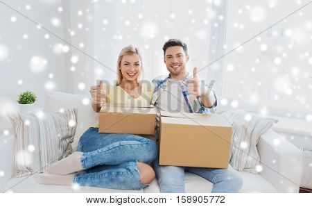 moving, people, repair and real estate concept - happy couple with big cardboard boxes showing thumbs up on sofa at new home over snow