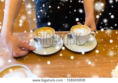 people, latte art, valentines day, christmas and winter holidays concept - hands of barista with heart etching in coffee cup over snow