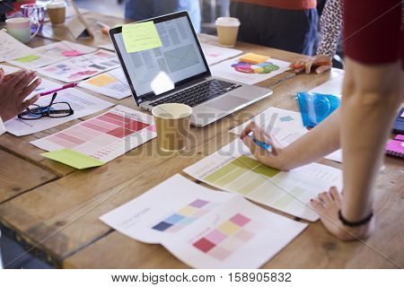 Close Up Of Designers Discussing Layouts And Color Schemes