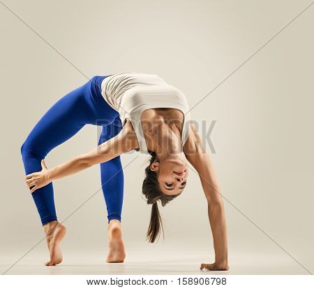 Young woman doing Yoga exercises. studio. Bridge pose - Urdhva Dhanurasana