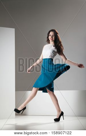 Happy beautiful woman in dark blue skirt and white top walking joyfully and cheerfully smiling. Isolated over grey and white background.
