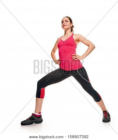 Young sportswoman full length stretching on white background