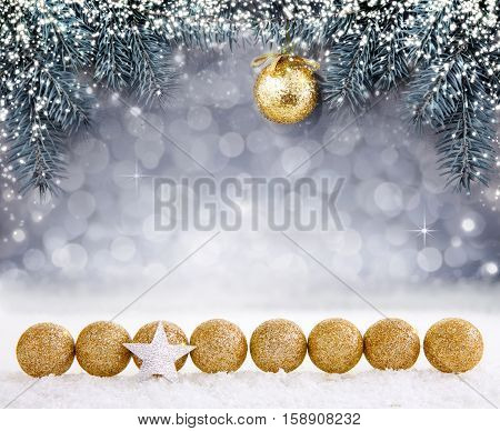 Golden Christmas ball on spruce branch isolated on gray background. Christmas background with shining lights and snow.