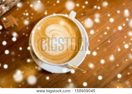 latte art, drink , love, christmas and valentines day concept - close up of coffee cup with heart shape drawing on cream froth over snow