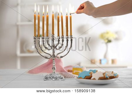 Female hand applying match to candles in menorah on wooden table. Hanukkah concept