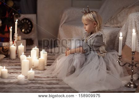 little girl in a princess crown. He sits and looks at a candle. Behind the tree