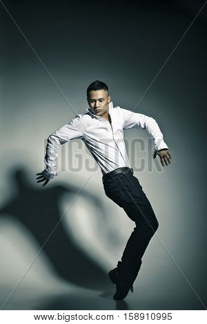 Modern style dancer posing on grey studio background