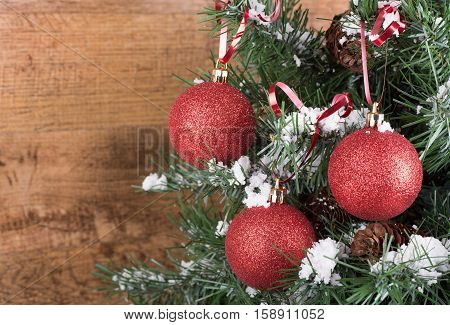Red Christmas ornaments hanging on a tree with a wood background