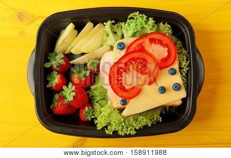 Lunchbox with dinner on yellow wooden background