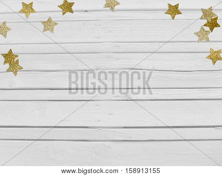 Christmas, New Year party mockup scene with golden star shape glittering confetti and empty space. White wooden background. Top view.