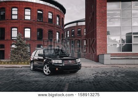 Moscow, Russia - September 25, 2016: Black Car Subaru Forester Parked Near Modern Red Buildings In M