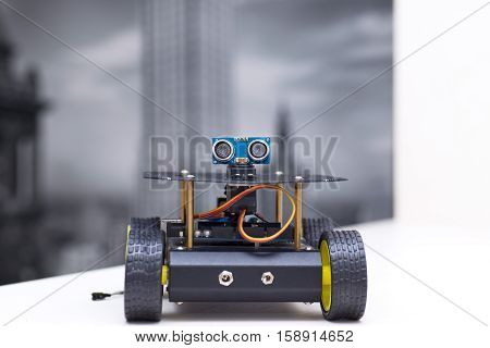 metallic robot on four wheels stands on a white table