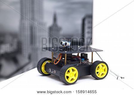 metal robot with yellow wheelsI stands on a white table