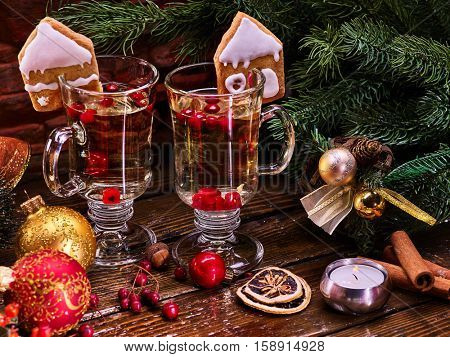 Close up Christmas still life with pair mug hot drink. Warming mulled wine with cookie in form of house and Christmas ball on spruce branch.