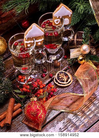 Top view Christmas still life with pair latte mug hot drink on wooden table. Warming mulled wine with cookie in form of house and Christmas ball on Christmas ribbon.