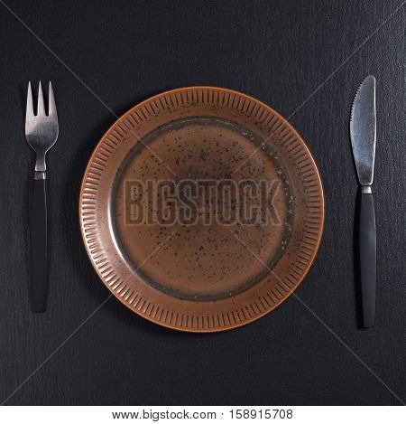 Empty old plate with fork and knife on black stone table top view