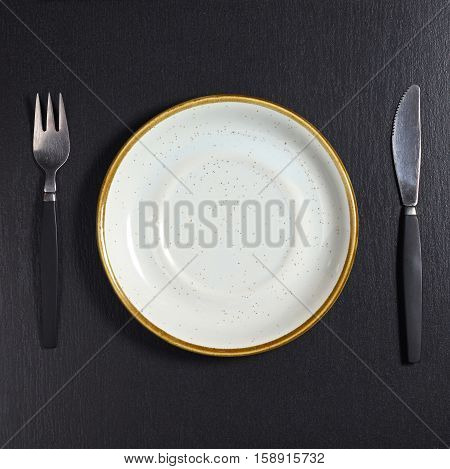 Empty plate on black stone background top view