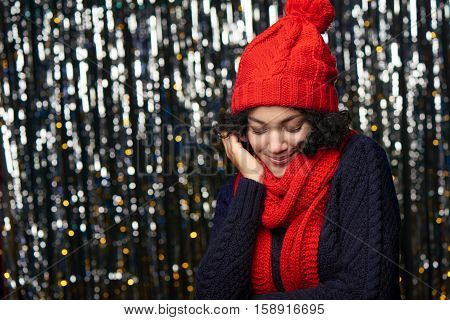 Christmas girl, young beautiful smiling wearing red knit hat and scarf over shiny background muffling into warm scarf