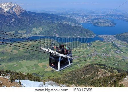 Mt. Stanserhorn, Switzerland - 7 May, 2016: people in a gondola of the Stanserhorn Cabrio cable car, summit of Mt. Pilatus and Lake Lucerne in the background. Stanserhorn Cabrio is the the world's first double deck open top cable car.