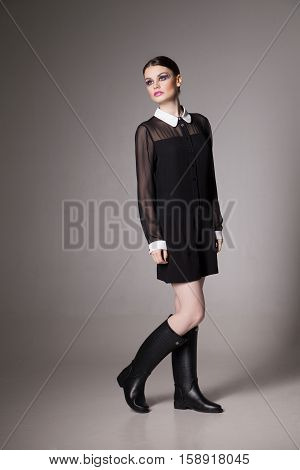 Fashion Image young woman in a stylish transparent  black dress with collar. Posing with one leg bent.
