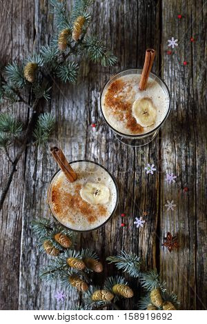 New Year's mood: two glasses of banana smoothie with cinnamon top view