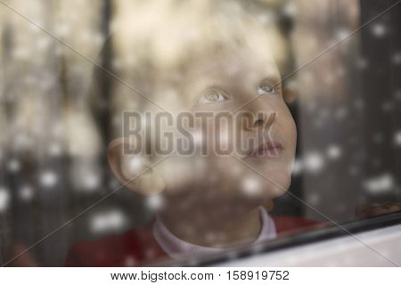 Young boy watching the first snow of the year