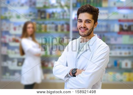 Portrait of pharmacist in pharmacy in the background is a woman pharmacist