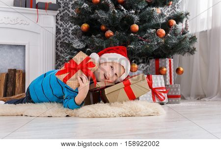 Cute happy boy in santa hat unwrap christmas present box on holiday morning in beautiful room interior. Male child open Xmas gifts near big decorated fir tree and fireplace. Winter holidays concept