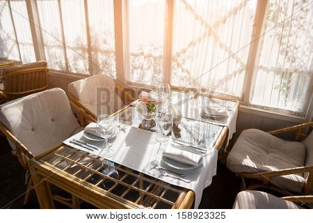 Table with plates and glasses. Chairs beside windows. Invite neighbours for breakfast. Hospitality and traditions.