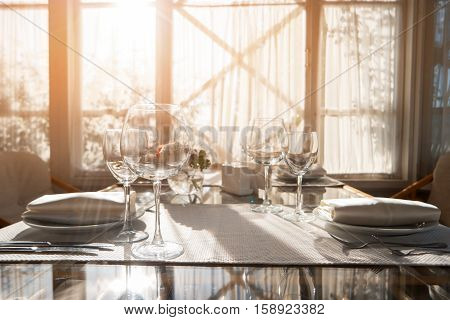 Glasses and plates on table. Dining table beside a window. Invite relatives for breakfast. Create perfect cleanliness.