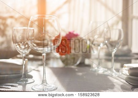 Empty wineglasses on white tablecloth. Glasses and sunshine. Invite friends for lunch. The perfect cleanliness.