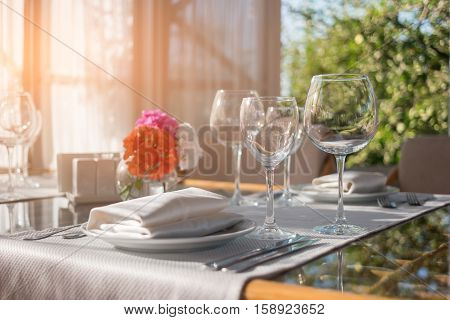 Plates and glasses on table. Dining table and sunshine. Invite neighbours for lunch. Create the perfect cleanliness.