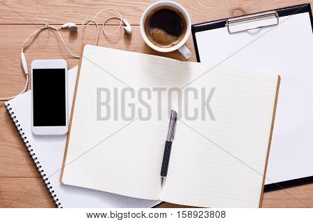 Notepad, diary and mobile with espresso coffee. Office supplies and business devices on wood office desk. Working table top view. Education or job background with copy space on paper sheet