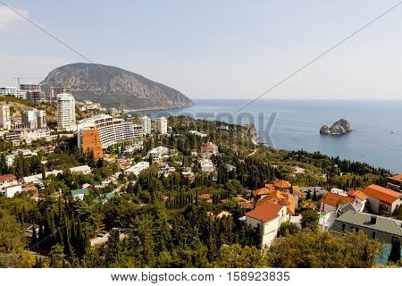 Gurzuf Crimea - September 7 2016: Rocky Beach with a protruding rock domes of churches and residential buildings located among different vegetation. The settlement Gurzuf and Bear Mountain Au-Dag . Crimea. View from Bolgatura Mountains in Gurzuf. Located