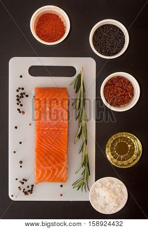 Salmon Fillet On White Board, Seasoning In Bowl On Black Background.