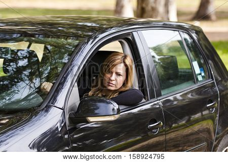 Female in a black car looking at the mirror