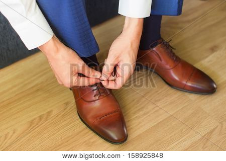 Male hands tied laces on the varnished brown shoes
