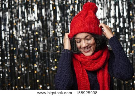 Christmas girl, young beautiful smiling wearing red knit hat and scarf over shiny background putting her hat on and looking down