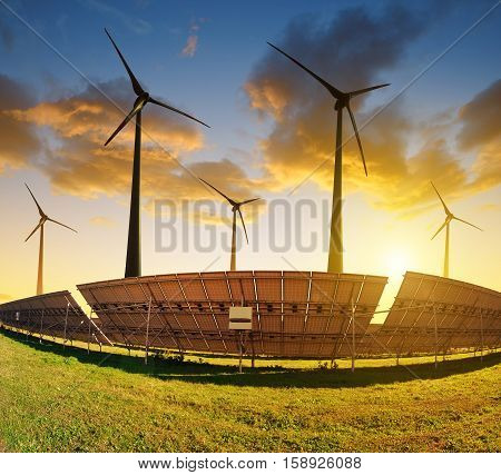Solar panels with wind turbines at sunset. Power plant using renewable energy.