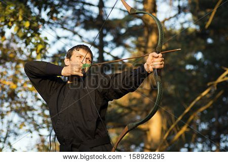 The archer in black kimono takes aim with bow and arrow in nature.