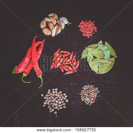 Spicy background with assortment of different hot chilies, allspice, brazilian peppers, garlic and bay leaves over rusty black wooden background. Top view.
