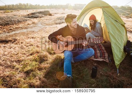 Couple with guitar in tent. singing songs