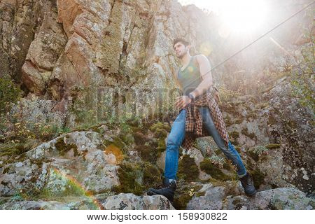 Traveling man with backpack walking on rock. full length image